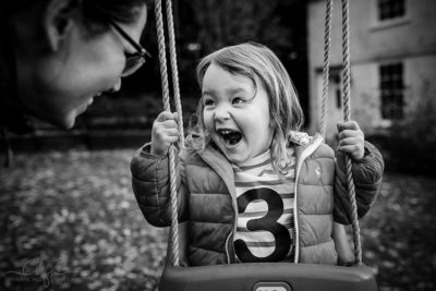 family life in pictures - lyla has an excited, expressive face on her swing